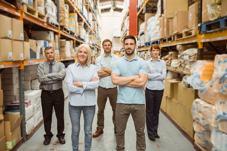 Smiling warehouse team with arms crossed in a large warehouse