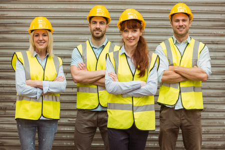yellow hard hat: Warehouse team with arms crossed wearing hard hat in a large warehouse