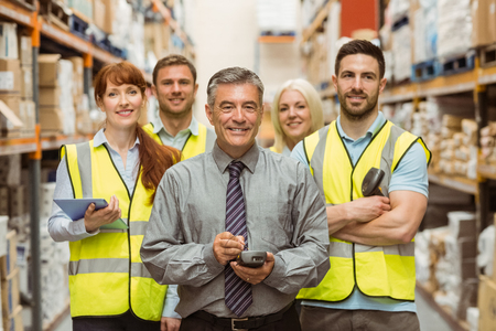 hand held computer: Smiling warehouse team with arms crossed in a large warehouse