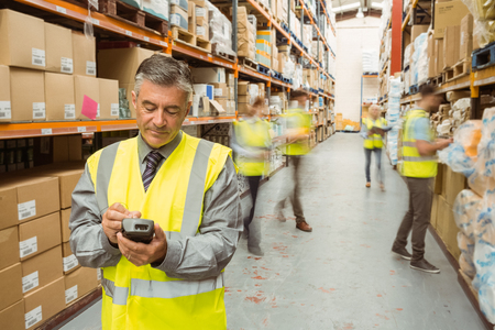 woman boss: Smiling male manager using handheld in a large warehouse
