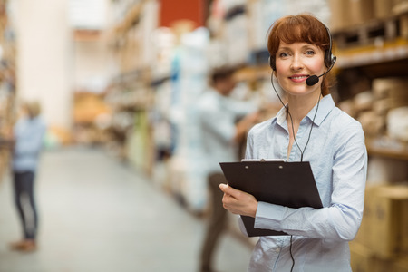 female worker: Manager wearing a headset while holding clipboard in a large warehouse