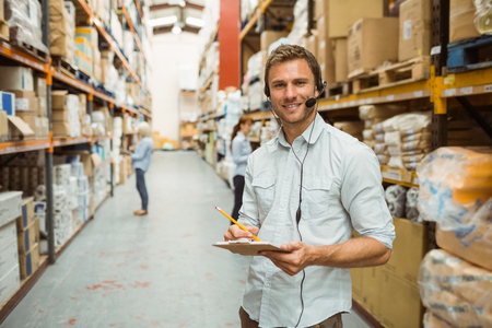 Warehouse manager wearing headset writing on clipboard in a large warehouse
