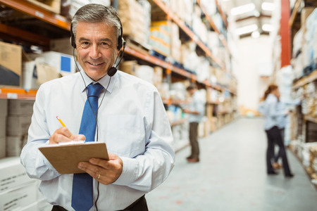 female worker: Smiling warehouse manager writing on clipboard in a large warehouse