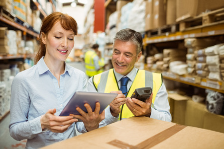 warehouse worker: Warehouse managers looking at tablet pc in a large warehouse