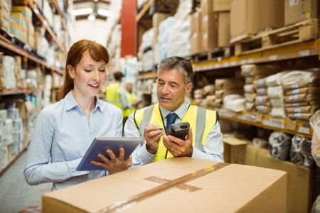 gestion empresarial: Los gerentes de almac�n mirando Tablet PC en un gran almac�n