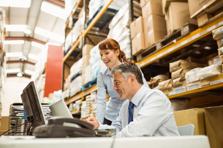 distribution warehouse: Warehouse managers working together on laptop in a large warehouse