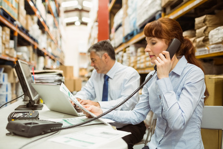 logistics: Manager working on laptop and talking on phone at desk in a large warehouse Stock Photo