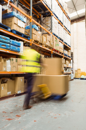 warehouse worker: Worker pushing trolley with boxes in a blur in a large warehouse