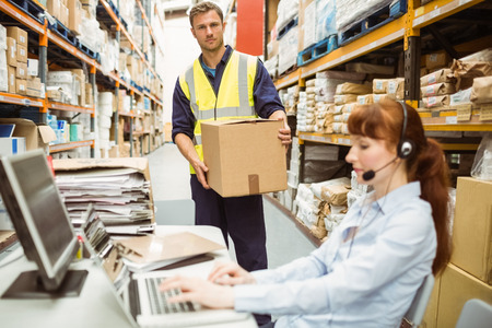 warehouse worker: Warehouse manager wearing headset using laptop in a large warehouse