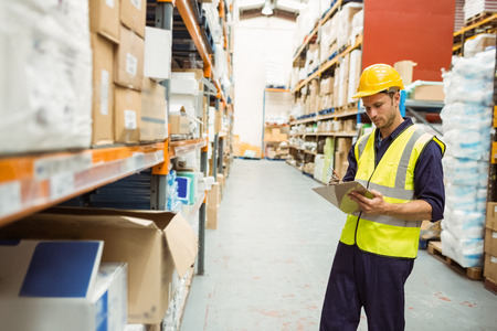 warehouse worker: Focused warehouse worker with clipboard in a large warehouse