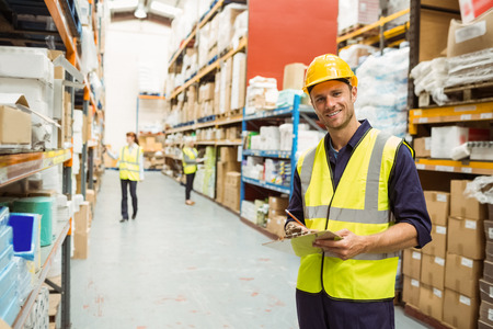 ouvrier: Entrepôt travailleur souriant à la caméra avec le presse-papiers dans un grand entrepôt