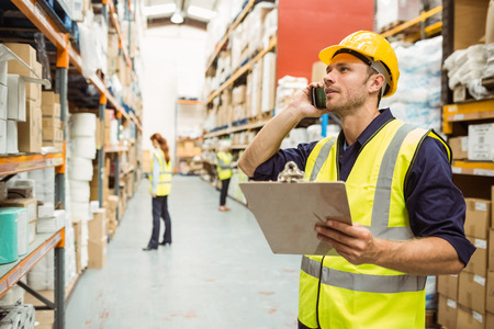 Warehouse worker talking on the phone holding clipboard in a large warehouse