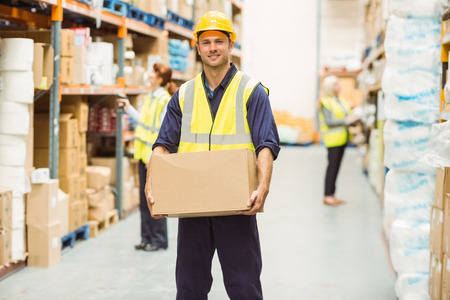 female worker: Warehouse worker smiling at camera carrying a box in a large warehouse