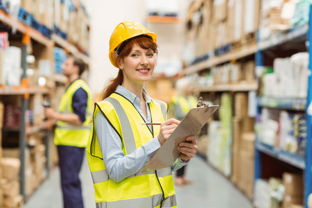 female worker: Smiling warehouse manager holding clipboard in a large warehouse