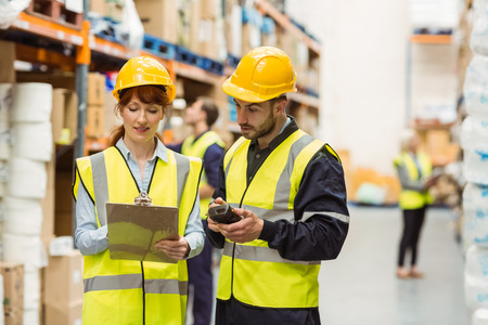 Warehouse manager talking with worker in a large warehouse Stock Photo
