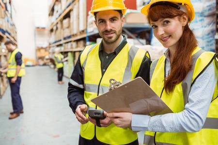 mujer trabajadora: Equipo Almac�n trabajar juntos con el portapapeles en un gran almac�n