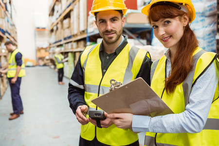 Warehouse team working together with clipboard in a large warehouse