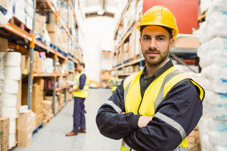 Smiling worker wearing yellow vest with arms crossed in a large warehouse Stock Photo