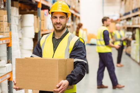 Magazijn werknemer glimlachen op de camera met een doos in een groot magazijn