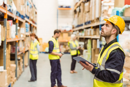 Focused warehouse manager writing on clipboard in a large warehouse