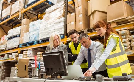 Warehouse managers en werknemer praten in een groot magazijn Stockfoto