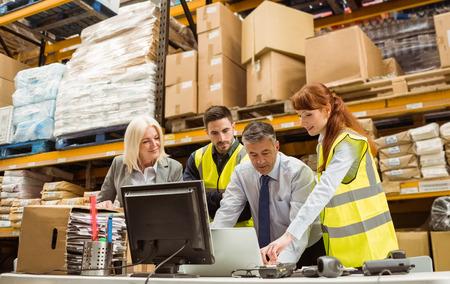 obreros trabajando: Los gerentes de almac�n y trabajador en la computadora port�til en un gran almac�n Foto de archivo