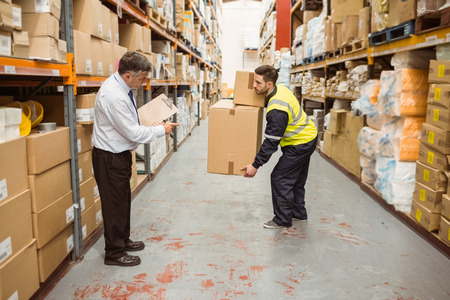 on the job training: Manager watching worker carrying boxes in a large warehouse