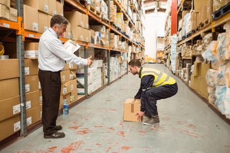Gestionnaire regarder travailleur transportant des boîtes dans un grand entrepôt Banque d'images