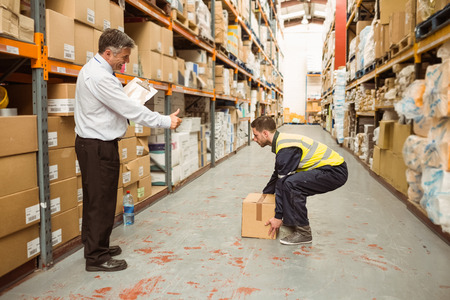 Manager watching worker carrying boxes in a large warehouse