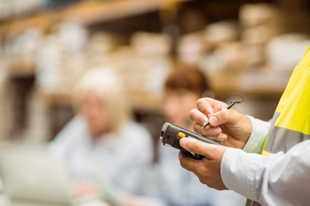 hand held computer: Close up of manager wearing yellow vest using handheld in a large warehouse