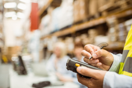 logistics: Close up of manager wearing yellow vest using handheld in a large warehouse