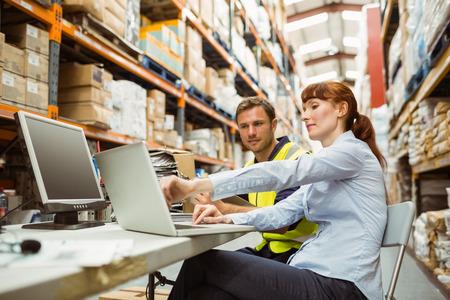 倉庫作業員と大規模な倉庫でのラップトップを見てマネージャー