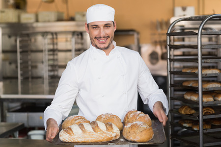 baker: Baker holding tray of bread in the kitchen of the bakery