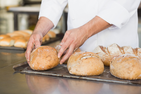 baked bread: Baker checking freshly baked bread in the kitchen of the bakery