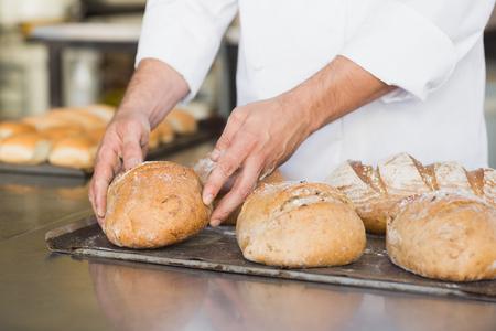 panadero: Panadero comprobación de pan recién horneado en la cocina de la panadería