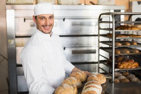 locales comerciales: Panadero feliz que muestra la bandeja de pan fresco en la cocina de la panadería Foto de archivo
