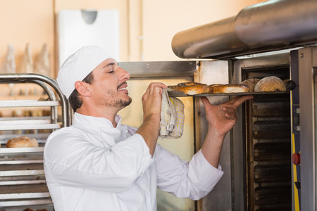 bakery oven: Happy baker taking out fresh bagels in the kitchen of the bakery Stock Photo