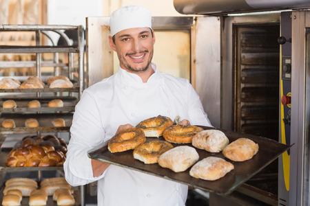 Gelukkig bakker met lade van vers brood in de keuken van de bakkerij Stockfoto