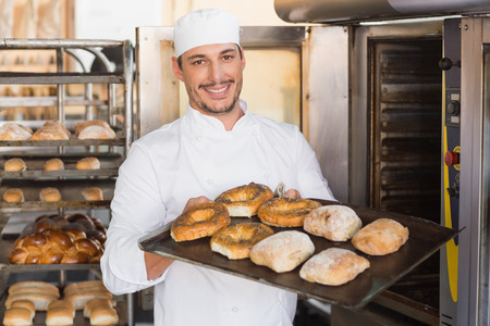 fresh bakery: Happy baker showing tray of fresh bread in the kitchen of the bakery