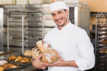 baker: Baker holding freshly baked loaves in the kitchen of the bakery