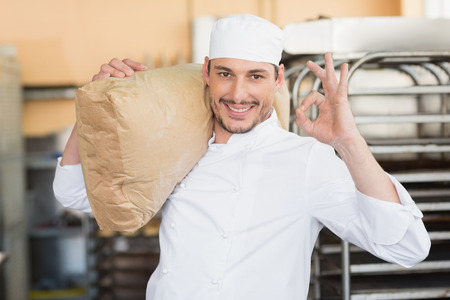 hotel staff: Smiling baker holding bag of flour in the kitchen of the bakery Stock Photo