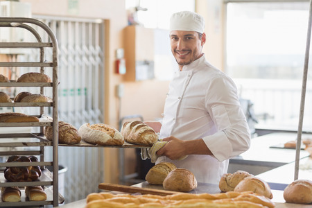 food and drink industry: Smiling baker holding tray of bread in the kitchen of the bakery