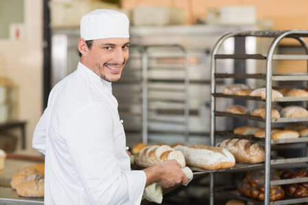 industrial kitchen: Smiling baker holding tray of bread in the kitchen of the bakery