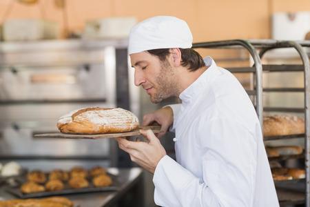 baker: Smiling baker smelling fresh bread in the kitchen of the bakery