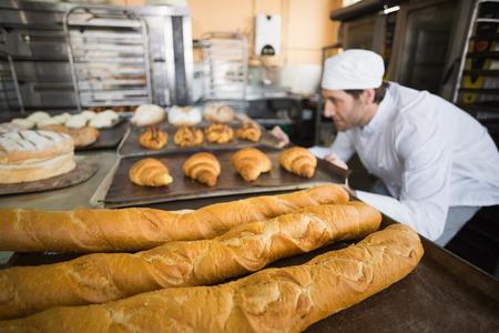 베이커는 갓 빵집의 부엌에서 빵을 구운 확인