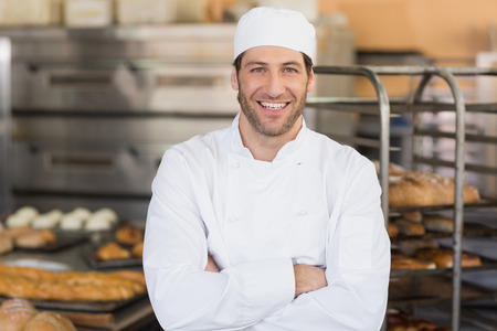 bakery store: Smiling baker looking at camera in the kitchen of the bakery