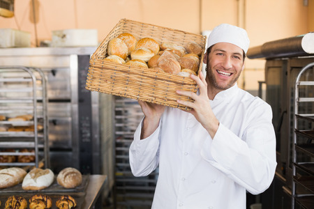 Baker holding basket of bread in the kitchen of the bakery
