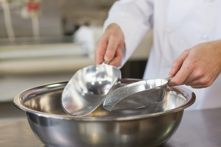 Baker holding scoops over bowl in the kitchen of the bakery photo