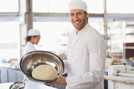 Baker showing dough in mixing bowl in the kitchen of the bakery photo