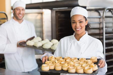 panadero: Baker, sonriendo a la cámara que sostiene la bandeja en la cocina de la panadería Foto de archivo